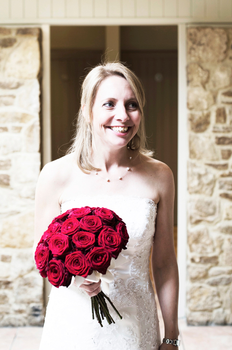 Bride holding bouquet of red roses and smiling