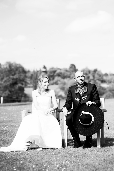 Black and white shot of bride and groom sitting in chairs during the ceremony