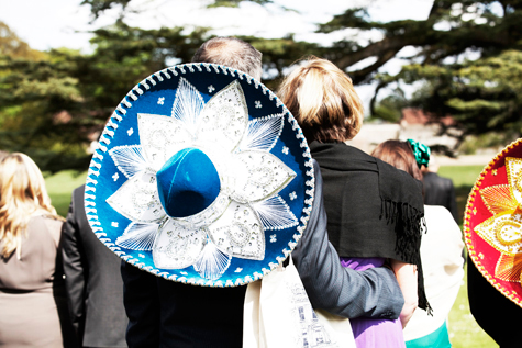 Shot of guests at ceremony from behind, with blue and white sombrero on mans back