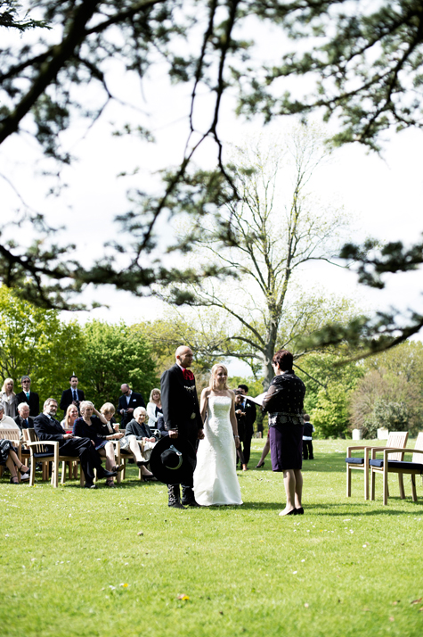 Wedding ceremony in the gardens with bride and groom standing in front of celebrant and guests seated behind