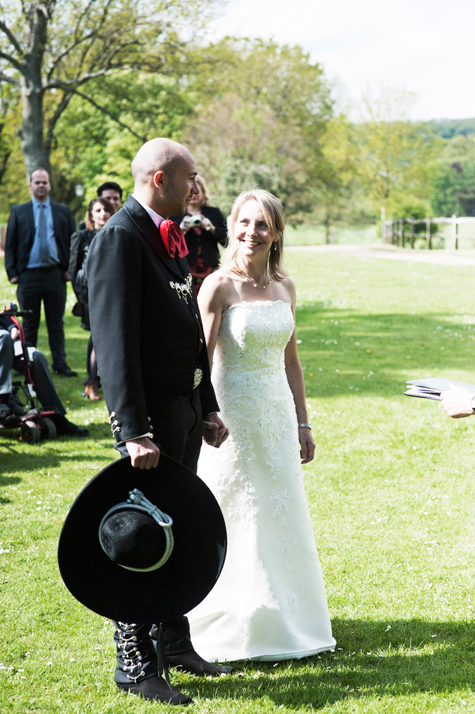 Groom and bride outside with guests, groom holding sombrero