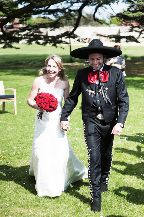 Bride and groom holding hands smiling and walking across the lawn
