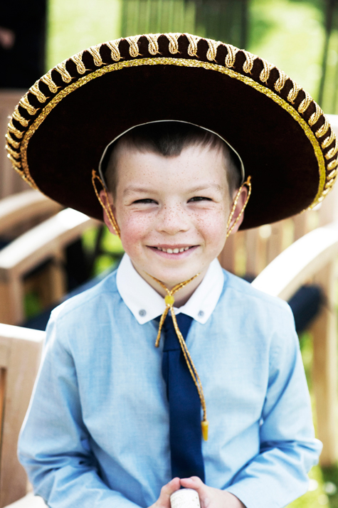 Portrait shot of little boy smiling wearing a black and gold sombrero
