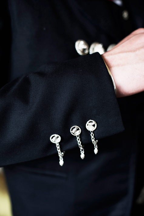 Detail shot of groom's jacket cuff and traditional silver buttons