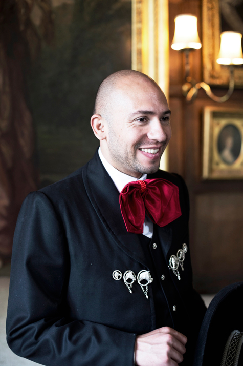 Groom smiling wearing traditional charro suit in venue