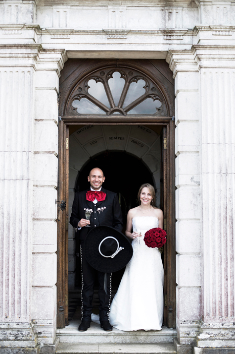 Bride and groom smiling in doorway of venue holding champagne glasses and bouquet