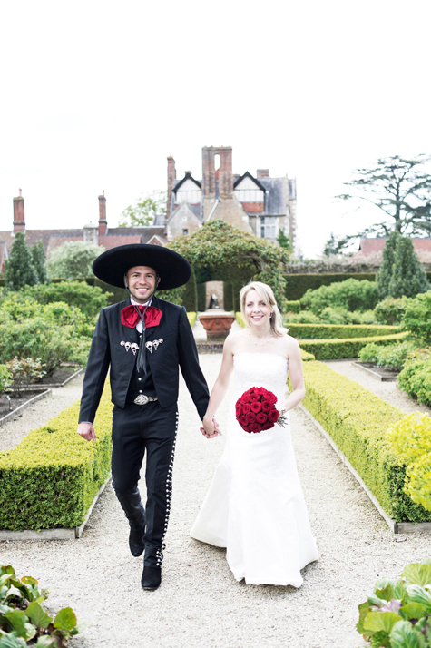 Bride and groom holding hands walking through the formal gardens of Loseley Park