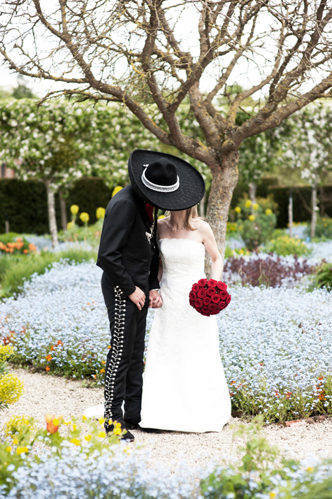 Groom kissing bride in flower garden with sombrero shielding her face