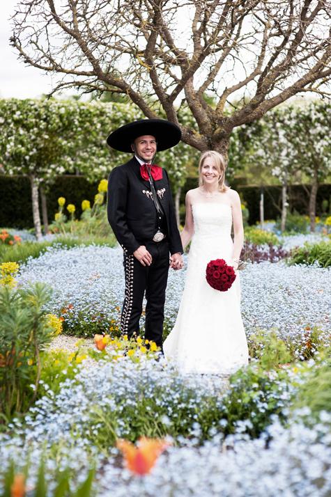 Bride with bouquet holding grooms hand standing in flower garden