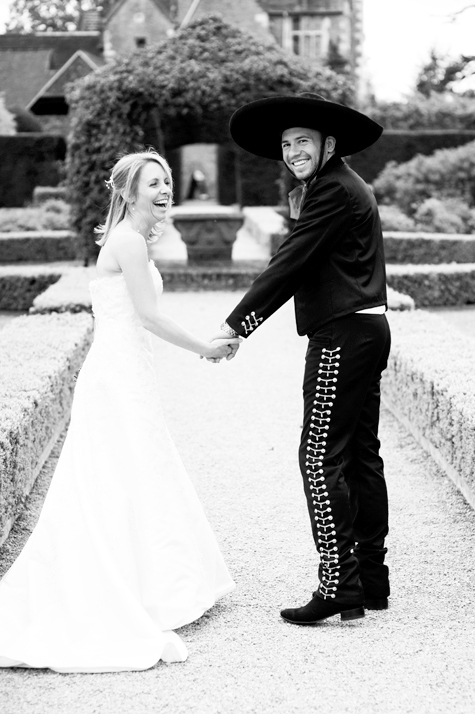 Black and white shot of bride and groom in formal gardens laughing and holding hands