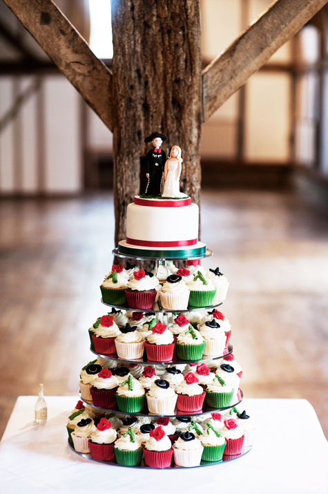 wedding cake with mexican groom and bride on top and colourful cupcakes decorated with sombreros, cactae and roses on stand underneath