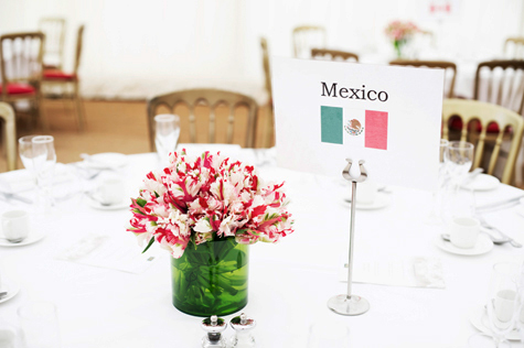 Table name 'Mexico' with flag image, next to floral table decoration in red, white and green