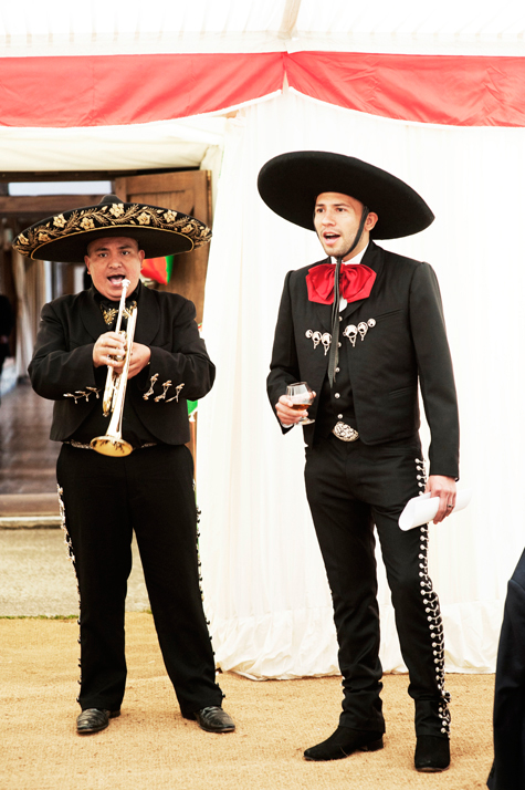 Groom singing song to bride, accompanied by Mexican man playing the trumpet