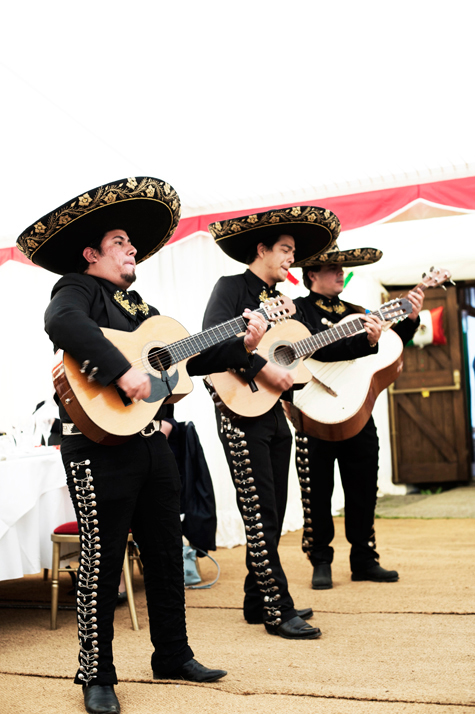 Three members of the Mexican band playing guitars in traditional costume