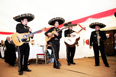 Mexican band in traditional costume playing guitars and trumpet at the reception