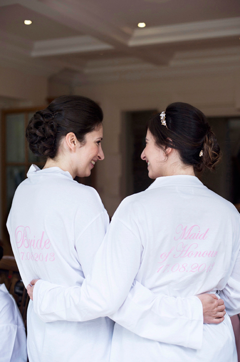 Bride and bridesmaid in their wedding bathrobes from behind