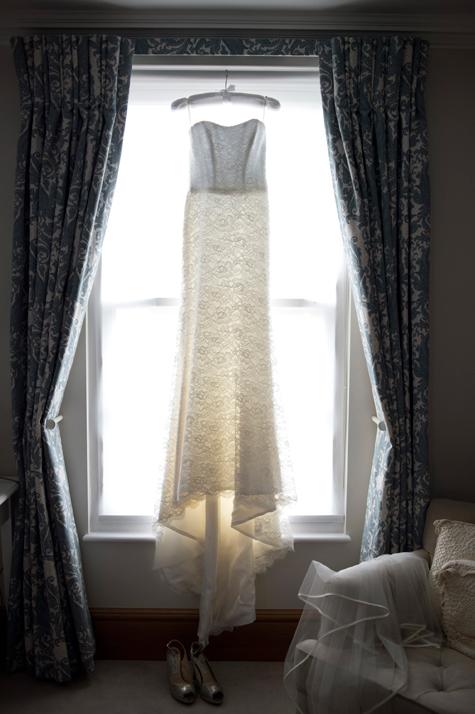 Wedding dress by Suzanne Neville hanging in window