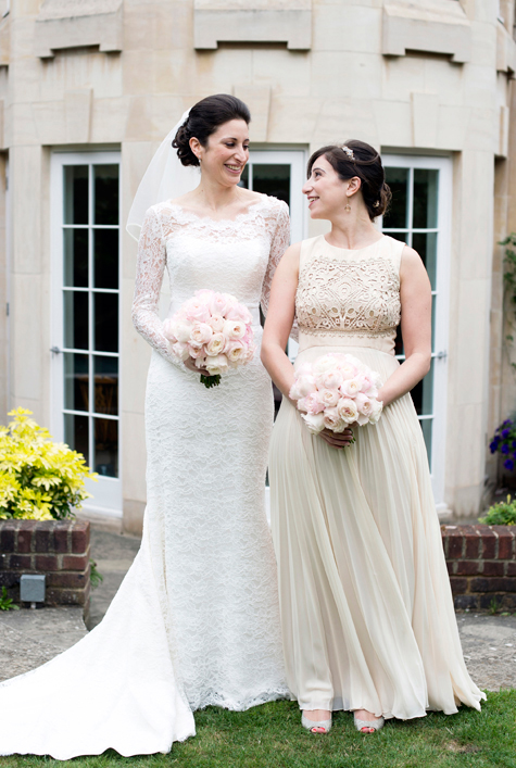 Bride and bridesmaid standing next to each other holding bouquets outside venue
