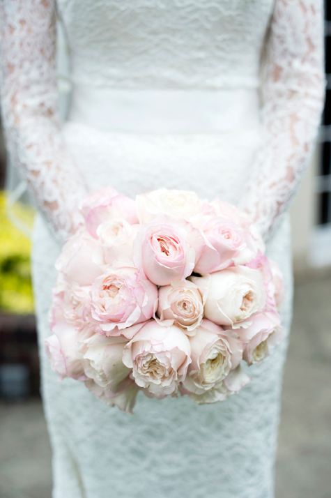 Detail shot of bride holding bouquet of pale pink roses