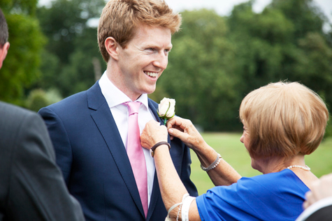 Groom smiling whilst buttonhole flower is attached by female guest