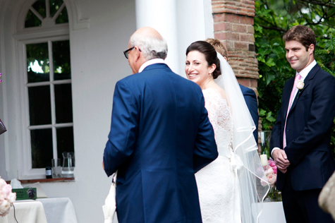Bride and father of bride with male guest outside Grotto