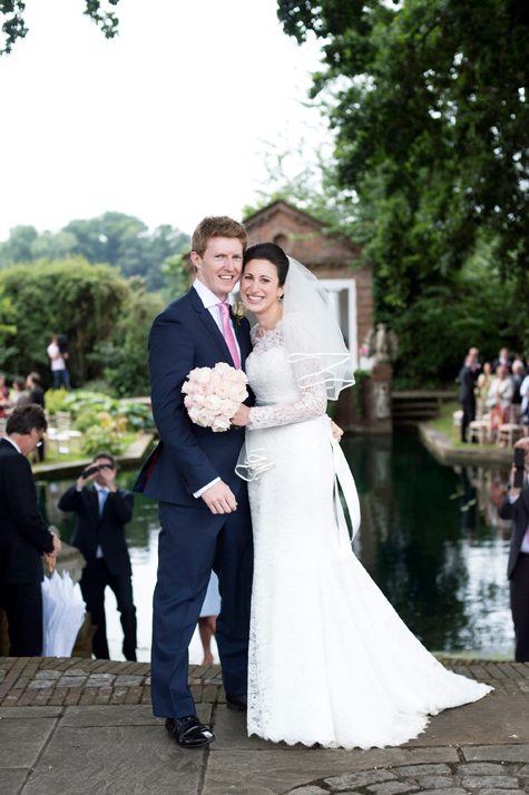 Bride holding bouquet next to groom in front of water in gardens