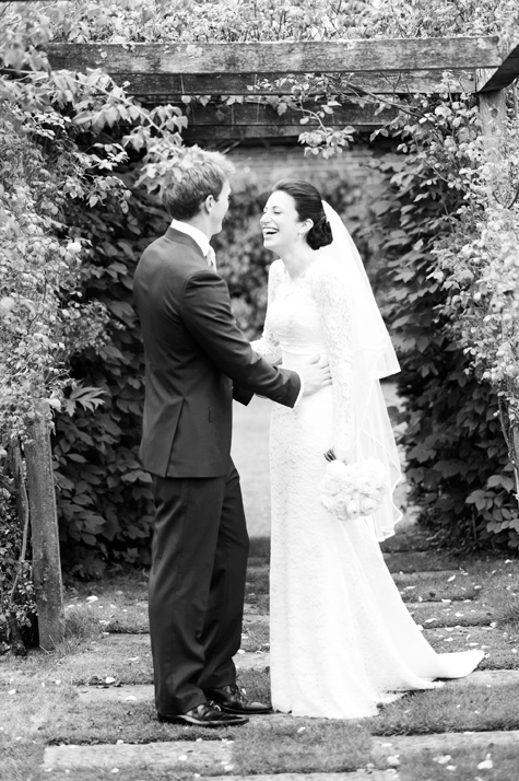 Black and white shot of bride and groom laughing holding each other in gardens