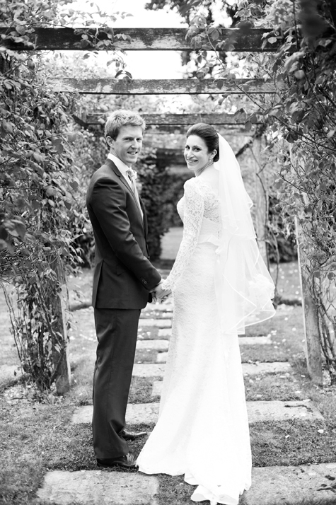 black and white shot of bride and groom holding hands and smiling in gardens