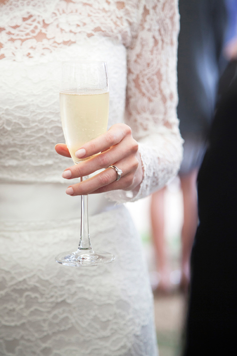 Detail shot of bride's hand holding glass of champagne