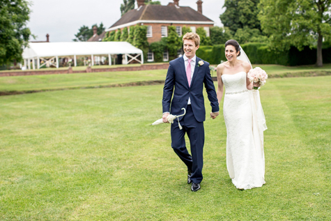 Bride holding bouquet and groom holding white umbrella walking across the lawn with marquee in background
