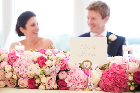 Bride and groom at wedding table with flower decorations and table name in foreground