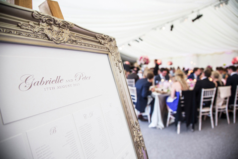 Table seating plan in marquee with seated guests in background