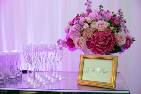 Detail shot of Gabi's bar with champagne glasses and pink flowers