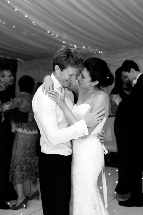 Black and white shot of bride and groom in each other's arms on dancefloor
