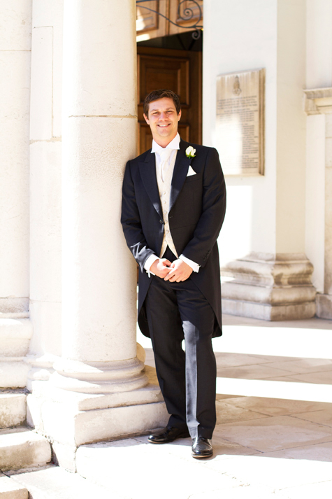 Groom in morning suit leaning against pillar