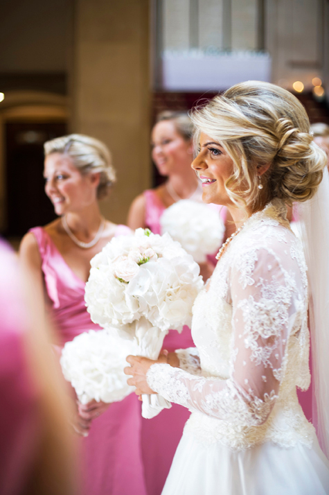 Bride holding bouquet of white flowers with bridesmaids dressed in pink in background