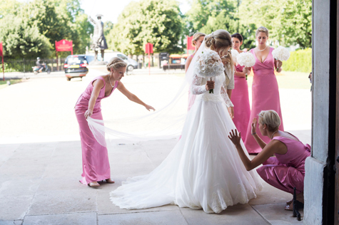 Bride at entrance of chapel, surrounded by bridesmaids dressed in pink straightening her veil and dress