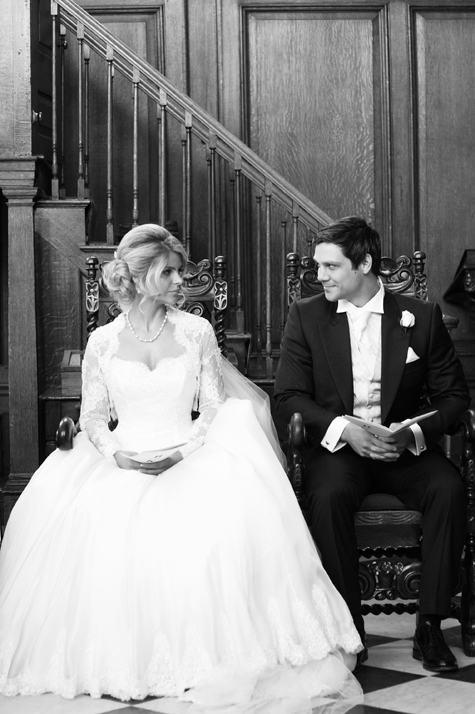 Black and white shot of bride and groom sitting next to each other during the service
