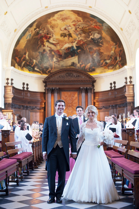 The newly married couple walking down the aisle together smiling, with Wren chapel ceiling above them