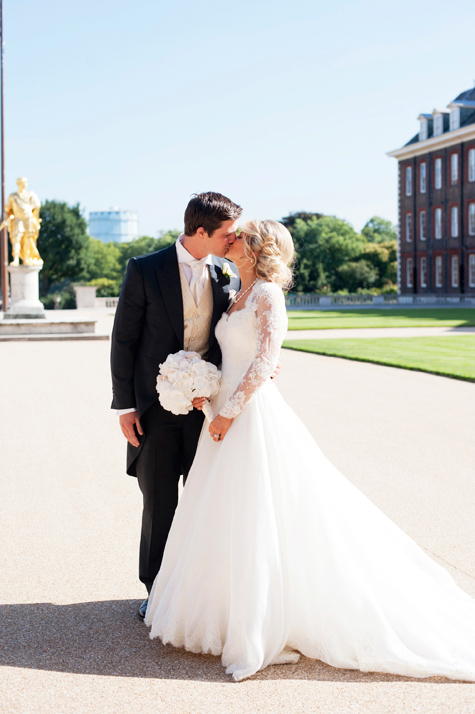 Bride and groom kissing outside the chapel, with gold statue behind