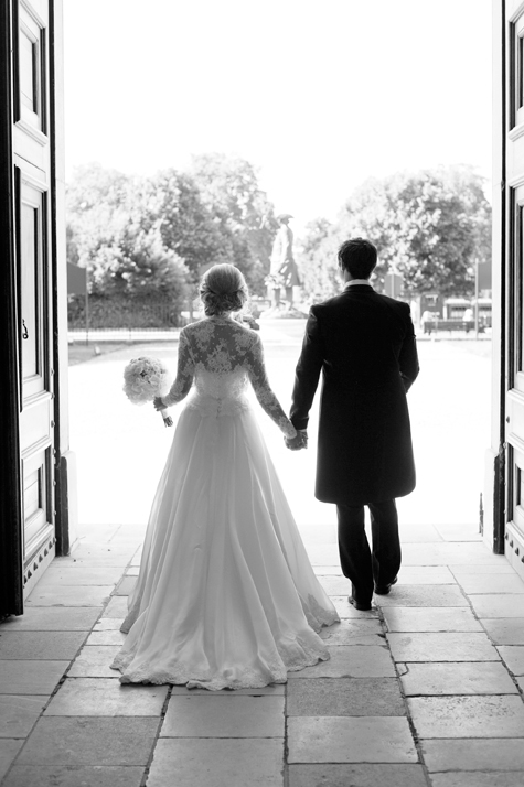 Black and white shot of bride and groom from behind, holding hands leaving the chapel