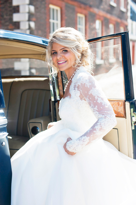 Bride smiling getting into the car