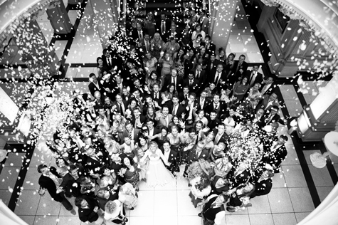 Black and white ariel shot of wedding party looking up with confetti falling from above