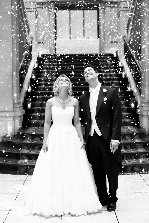 Black and white shot of bride and groom looking up in front of staircase with confetti falling on them