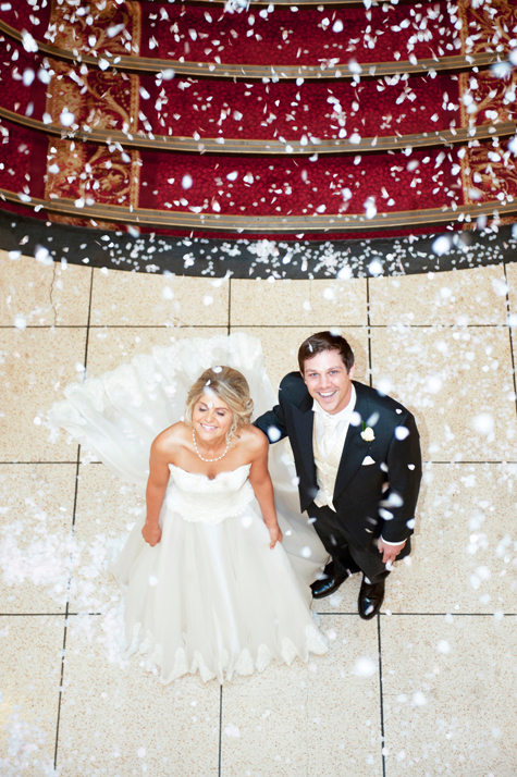 Ariel shot of bride and groom looking up as confetti falls from above