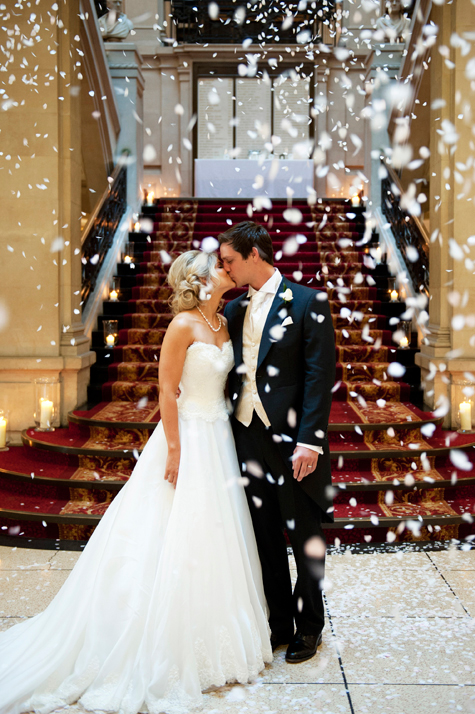 Bride and groom kissing in front of staircase with confetti falling around them