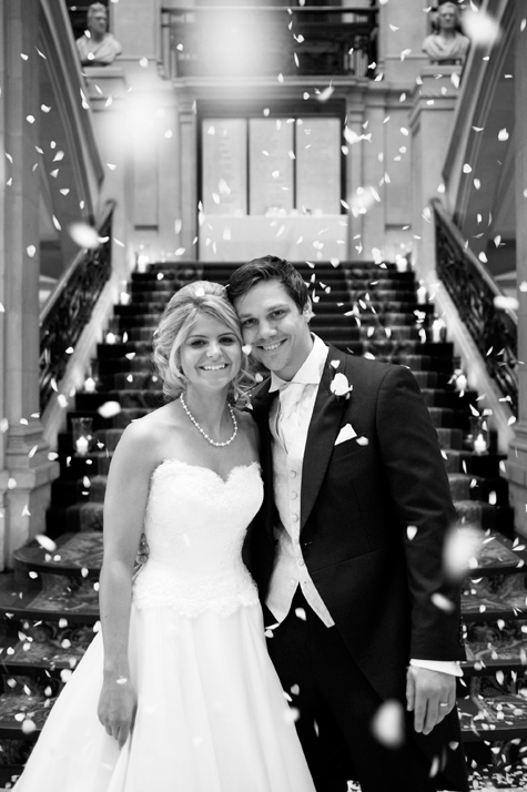 Black and white shot of bride and groom smiling with confetti falling behind them