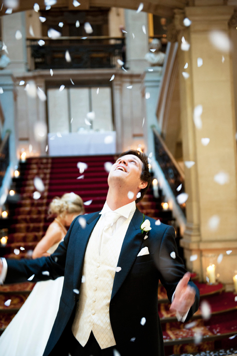 Groom looking up into confetti falling from above and smiling
