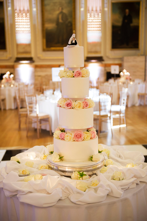 Four tiered wedding cake on table in reception room