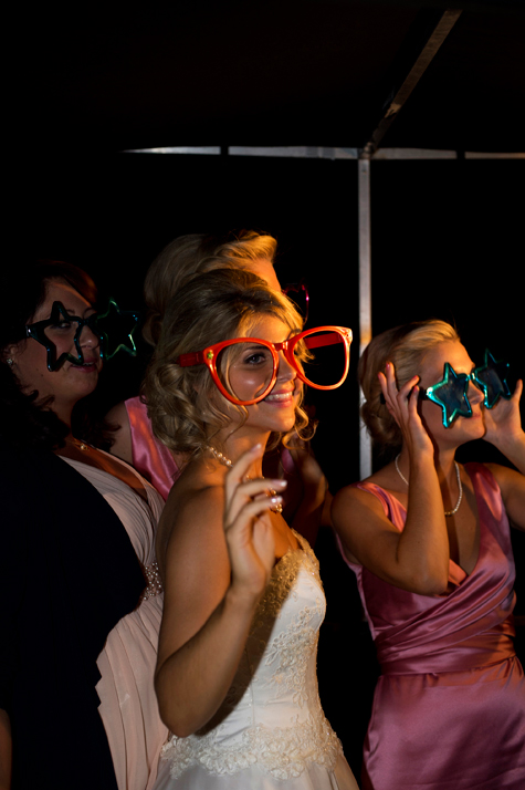 Bride and guests wearing giant novelty glasses